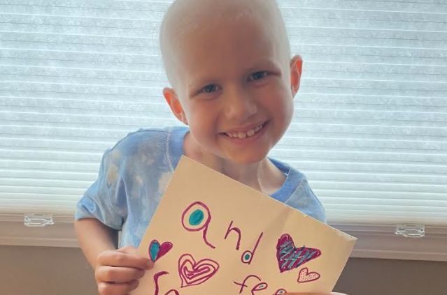 Chloe Marzilli smiles while holding up a sign decorated with hearts and a rainbow that says