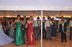 The DJ attracts the most people when he plays 'The Cotton Eyed-Joe,' a jig everyone seems to know by heart. Seniors Darcy Foreman and Becca Lieb lead everyone in the dance, standing in the front with their colorful gowns.