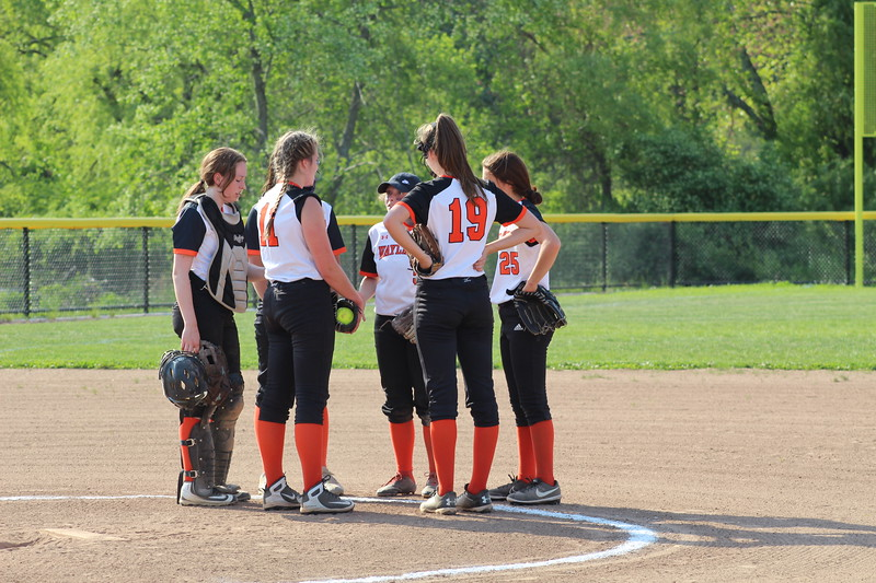 The fielders all huddle together to strategize the game as they wait for the next inning to begin.