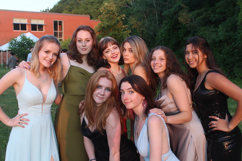 A group of senior girls gather together for a golden hour photo shoot.