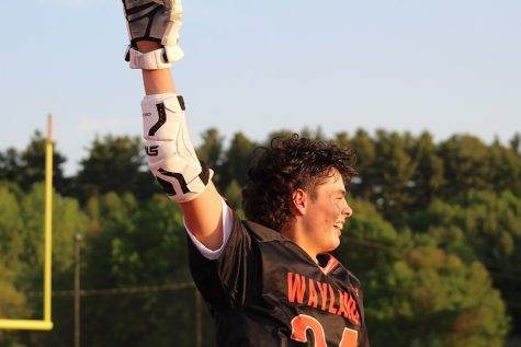 Junior Charlie Bolivar takes off his helmet, revealing his glee about Waylands triumph with a smile and throwing his arm up in the air.
