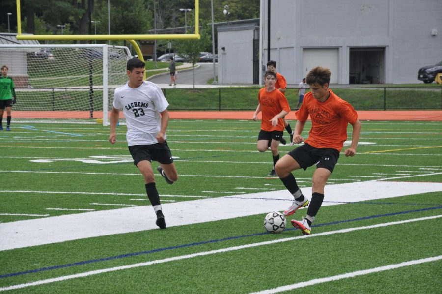 Senior Garrett Spooner runs with the ball and performs a maneuver to dodge the opponent who is actively trying to steal possession.