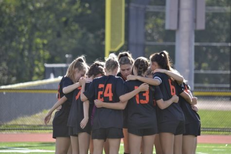 The Wayland girls soccer team comes together for a team huddle before the game kicks off. The Warriors look to carry the momentum into Thursday against Boston Latin.