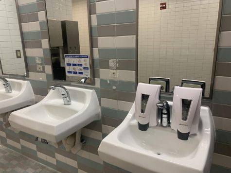 Two soap dispensers rest on the sink after being ripped off from its usual place.