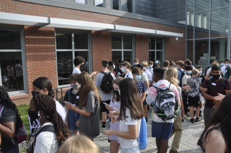 The ninth-graders stand in line as everyone begins to enter the high school building for the start of orientation.