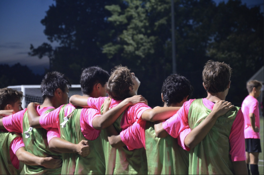 As the game began, the players on the sideline held each other to show their support for their teammates. While players were not currently playing in the game, they wore a green pinnie over their uniforms.