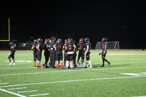 The Wayland offensive line huddles before the play. They strategize about how they are going to score.