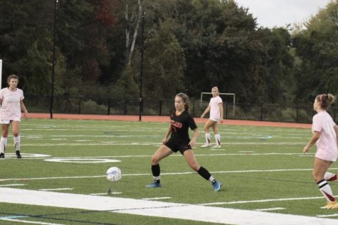 Freshman Zoe Mittelsteadt slides to get to the ball and prevent Waltham from possessing it. She has used her skills to dominate in the midfield. I feel more pressure being one of the youngest on the team because I dont want to let my team down, and I want to help them out as best I can, Mittelsteadt said.